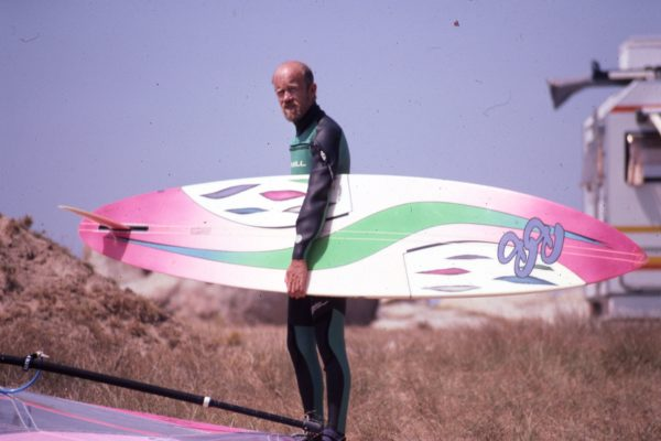 Oldschool picture of a men holding his windsurfing board