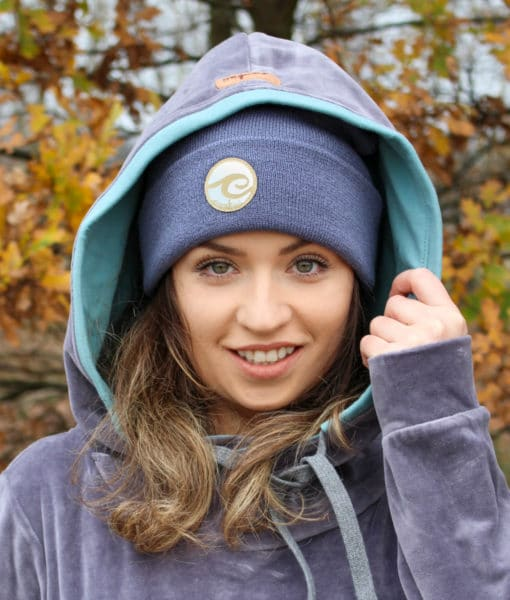 Surf beanie in anthracite colour worn by surf girl in autumn forest with velvet snug surf hoodie outfit, holding gently left side of the hood with the hand.