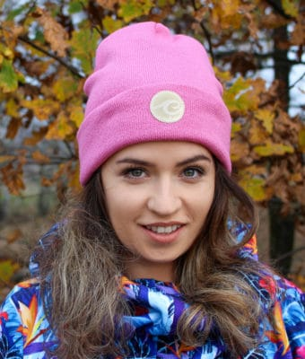 Surf beanie in dark rose colour worn by surf girl in autumn forest with leafs background.
