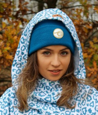 Surf beanie deep ocean worn by surf girl in autumn forest with panthera surf hoodie outfit.