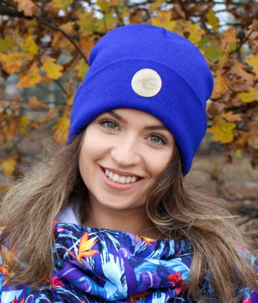 Surf beanie in indigo colour worn by surf girl in autumn forest in the background.