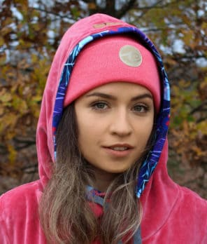 Surf beanie in salmon colour in autumn forest worn by surf girl.