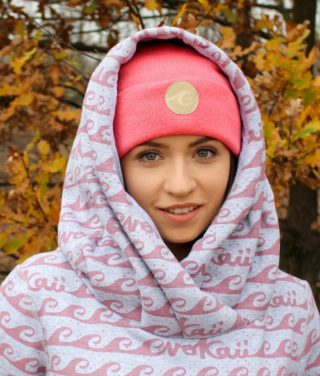 Surf beanie in salmon colour in autumn forest worn by surf girl with autumn leafs background.